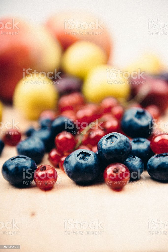 Blueberry, red currant, plums, peaches on wooden background royalty-free stock photo