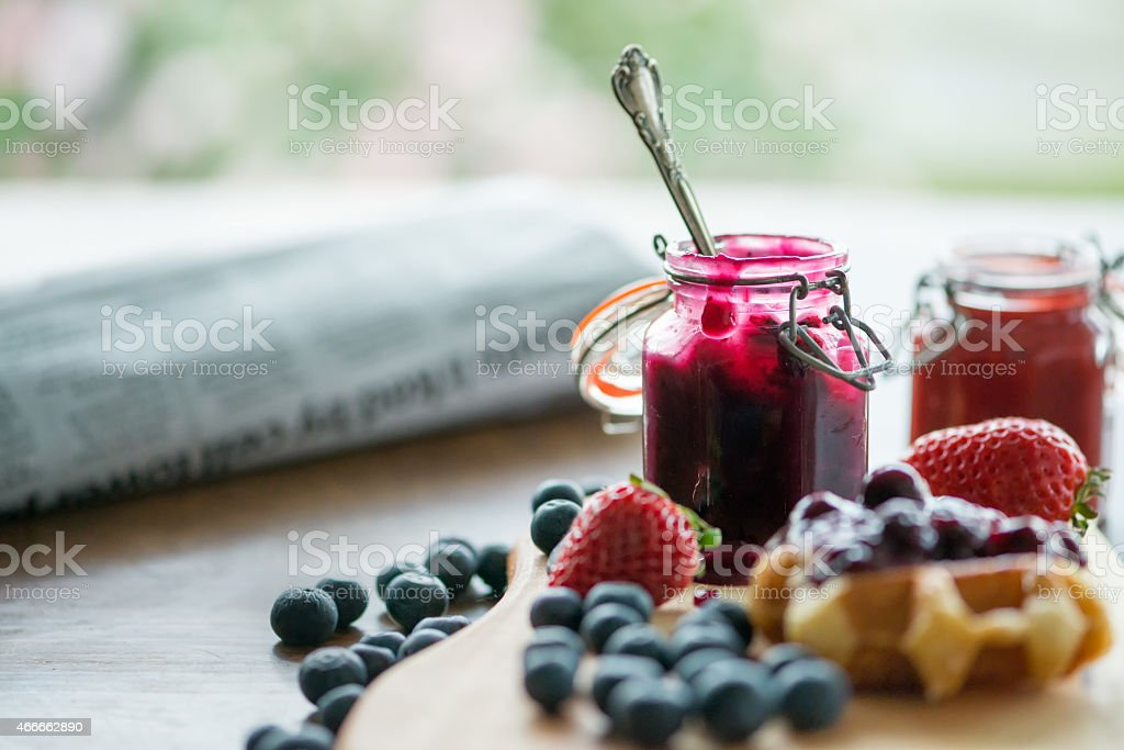 Blueberry, Strawberry Sauces, Waffle, Fresh Fruit, Newspaper, Against Garden Background stock photo