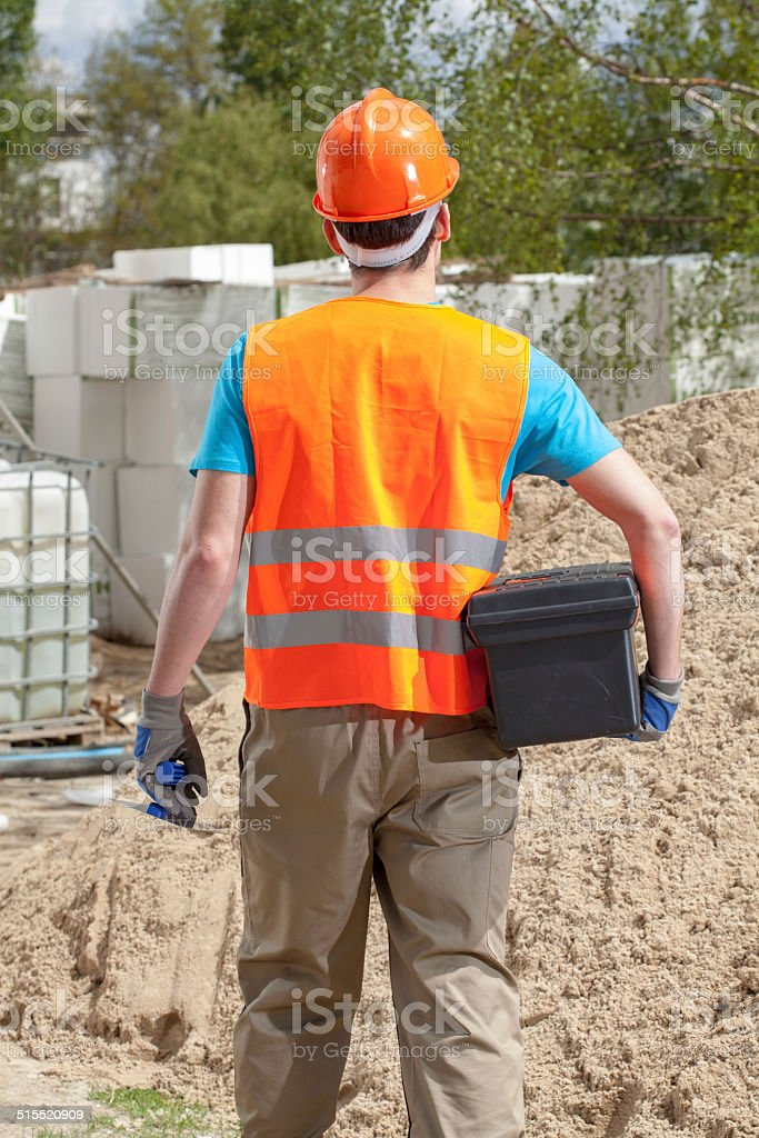 Blue-collar worker with toolbox and grout float stock photo