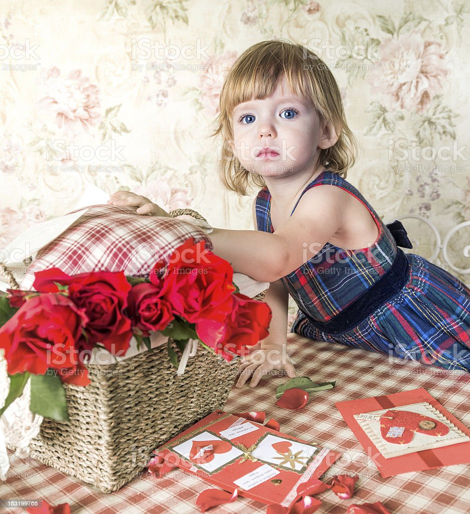 Blue-eyed baby and basket with roses royalty-free stock photo