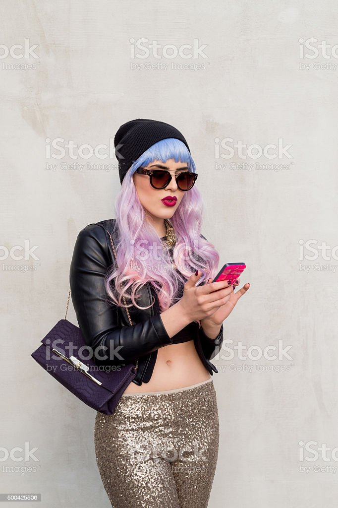 Blue-pink hair carefree girl texting on smart phone outside stock photo