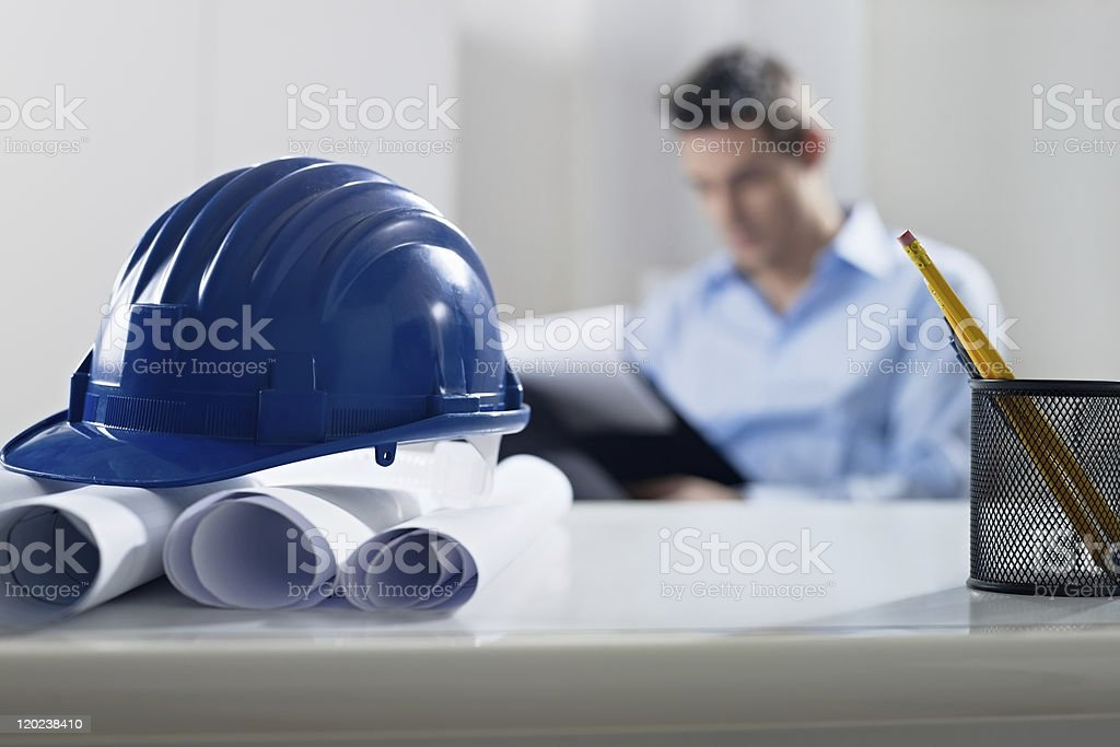 Blueprints and hardhat with man in the background stock photo