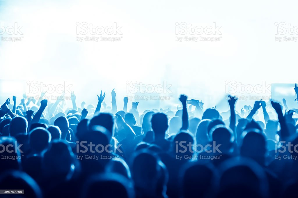 Blues hued concert crowd with arms raised stock photo