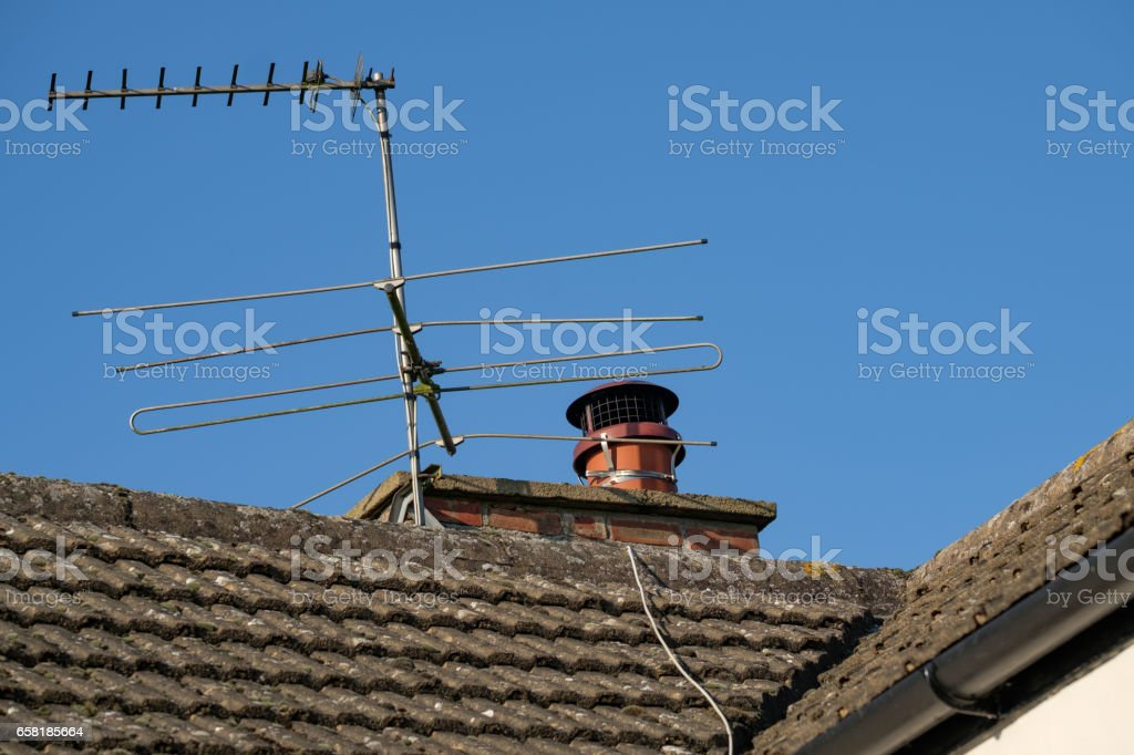 Bluntisham, Cambridgeshire, UK, 22 January 2017: Detailed view of an old cottage roof showing the tiling design, together with TV and Radio antennas strapped to the adjacent chimney stack. stock photo