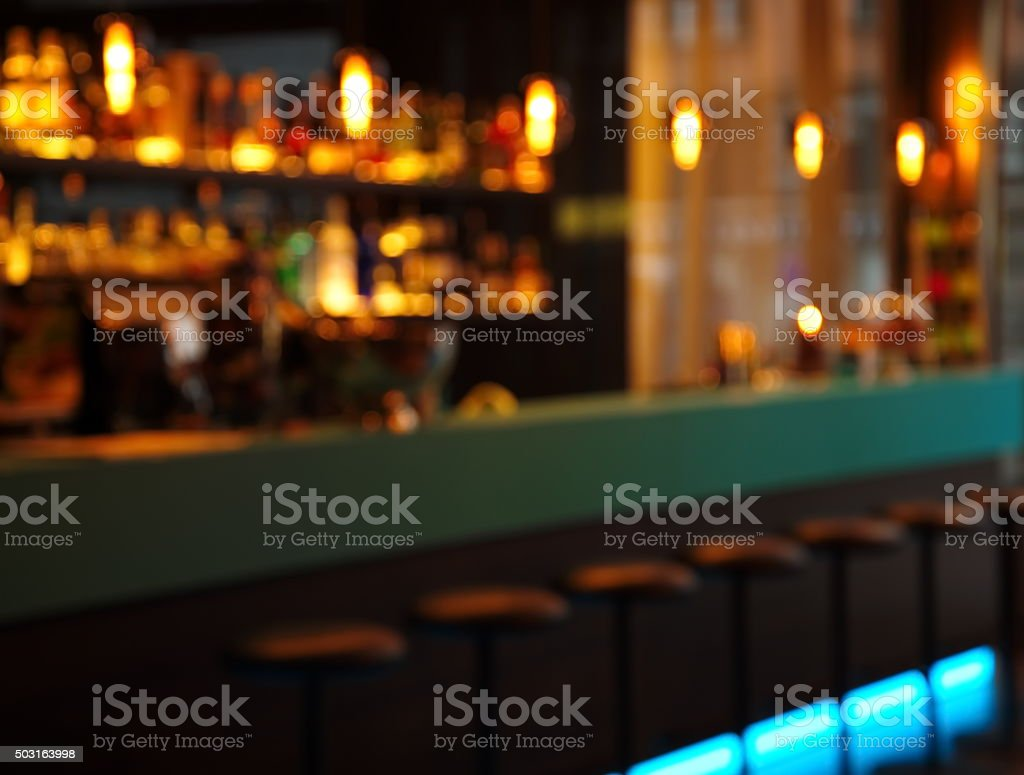 blur alcohol drink bottle and stool in pub iat night stock photo