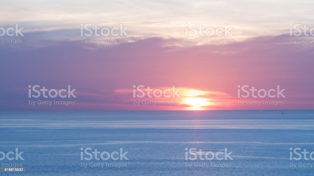 Blur beautiful soft blue and orange sky above the sea. Sunset in...
