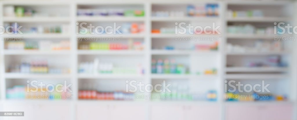 blur pharmacy store shelves filled with medicines arranged in shelves...