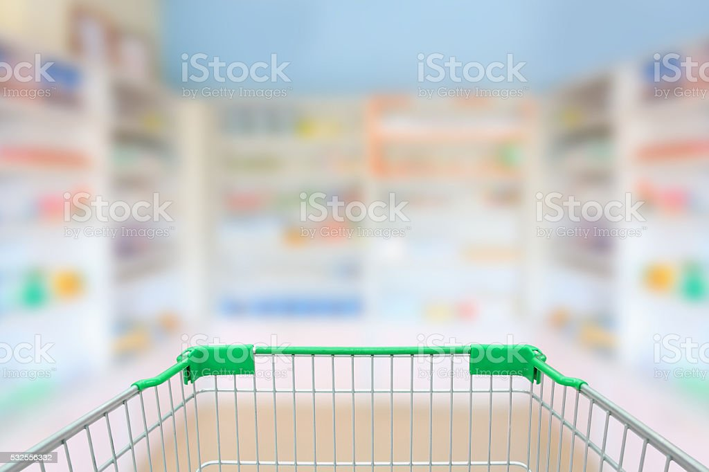 blur shelves of drugs in the pharmacy with shopping cart stock photo