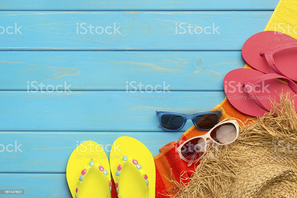 Blur wooden deck with slipper thongs, straw hat and sunglasses royalty-free stock photo