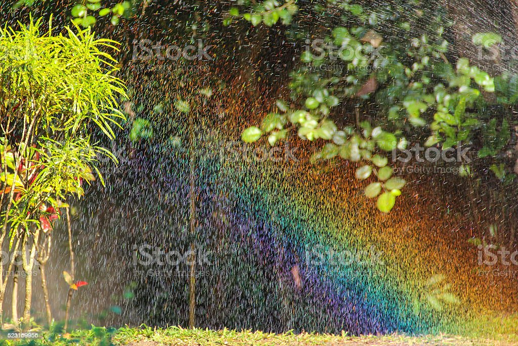 Blurred background: Bright rainbow in drops of flowing water stock photo