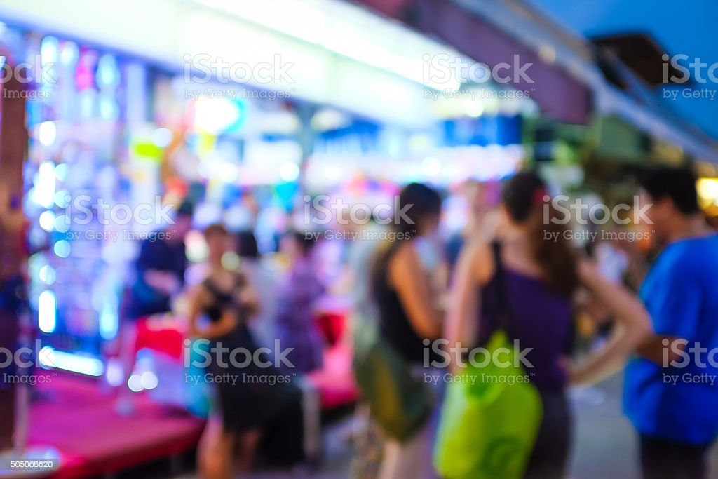 Blurred background of people shopping at night market vector art illustration