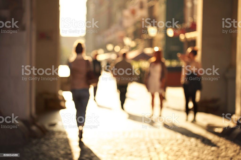 Blurred background of unrecognizable persons rushing through the arch...