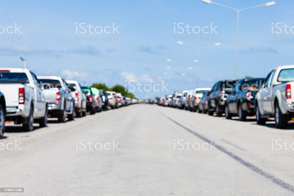 blurred background row of parked cars in parking lot stock photo