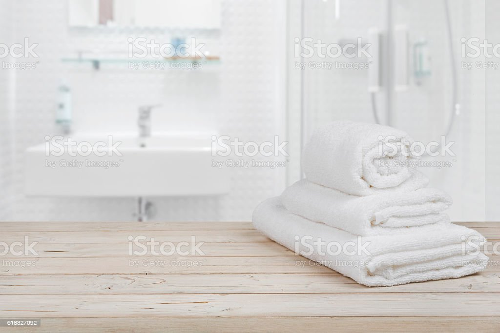 Blurred bathroom interior background and white spa towels on wood stock photo