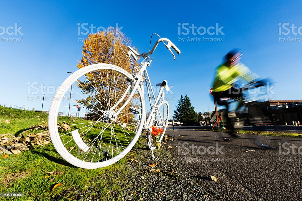 Blurred bicyclist passes a Ghost Bike stock photo