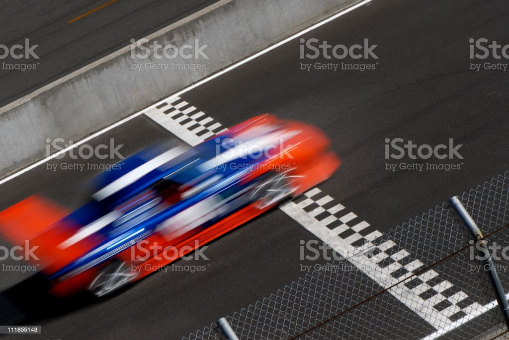 Blurred Blue Orange Race Car Crossing Checkered Finish Line stock photo