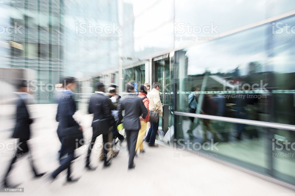 Blurred Business People Entering Office Building Through Glass Doors stock photo