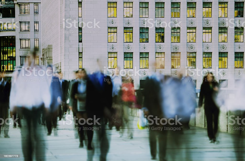 Blurred business people walking in front of illuminated office building stock photo