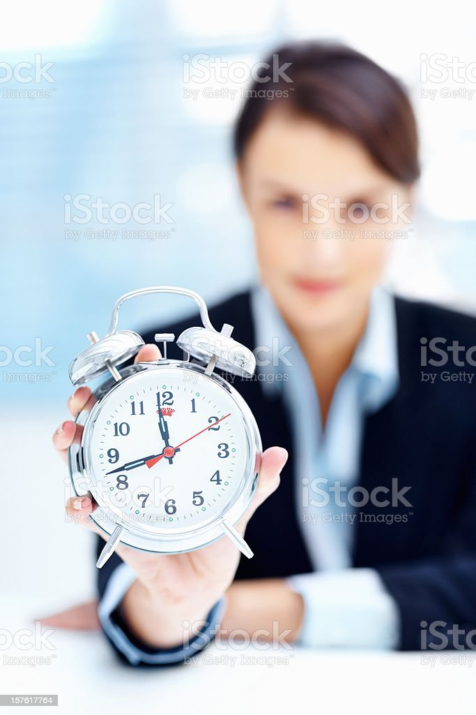 Blurred business woman showing you an alarm clock royalty-free stock photo