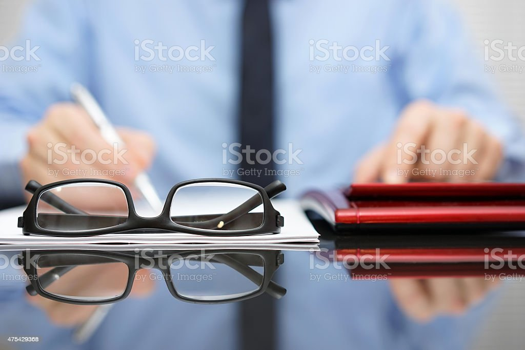 blurred businessman is working in office , focus is on eyeglasses stock photo