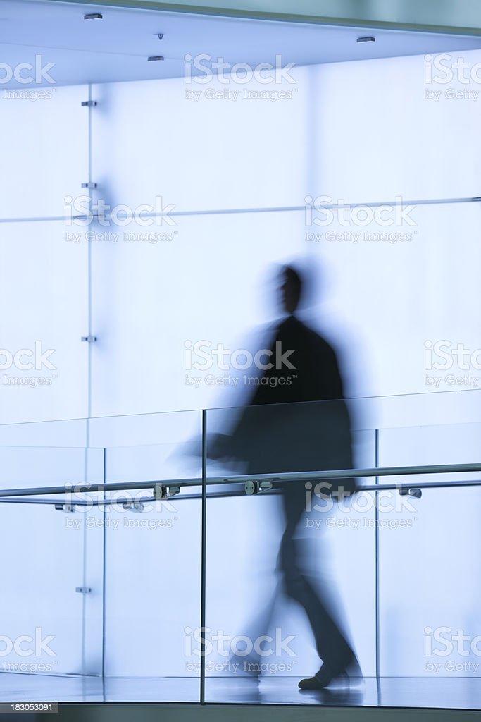 Blurred Businessman Walking in Glass Corridor royalty-free stock photo