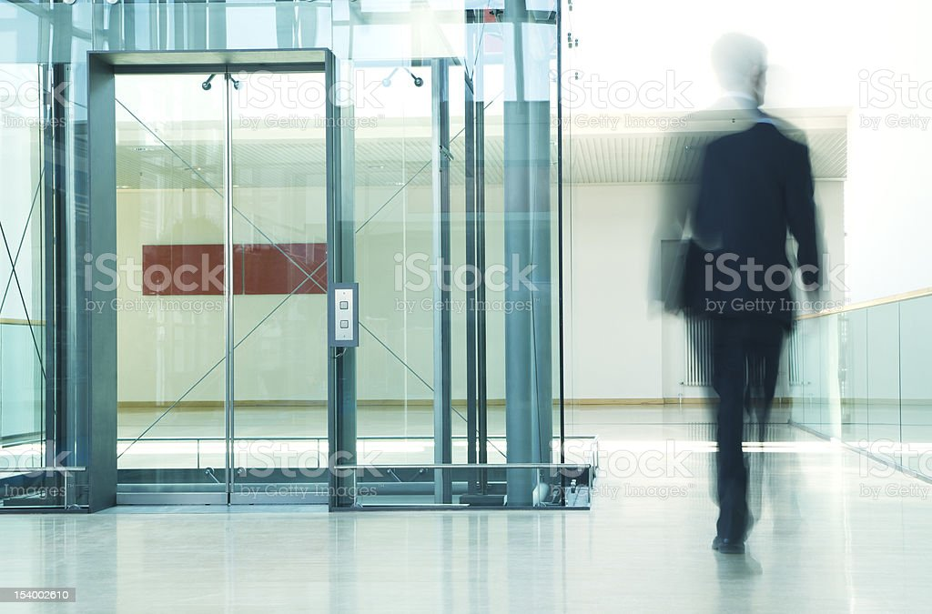Blurred Businessman Walking Past Elevator in Office Corridor royalty-free stock photo