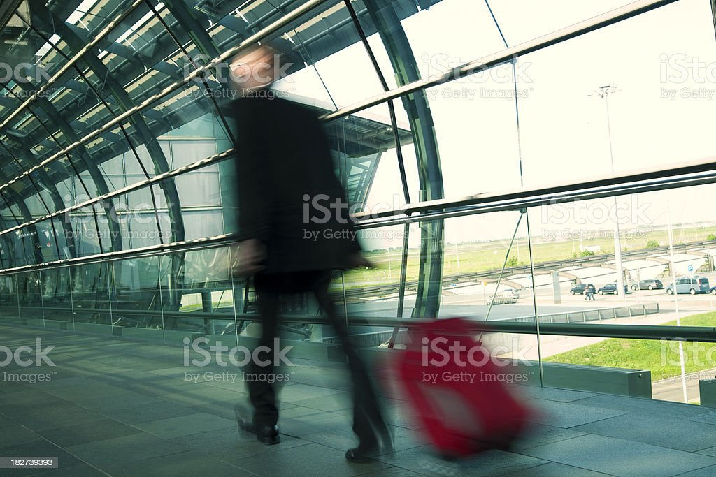 Blurred Businessman Walking quickly with Luggage down Hall in Airport royalty-free stock photo
