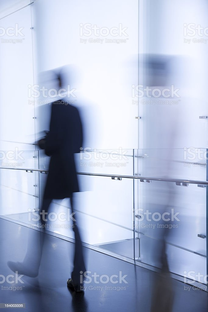Blurred Businessmen Walking in Modern Glass Corridor royalty-free stock photo