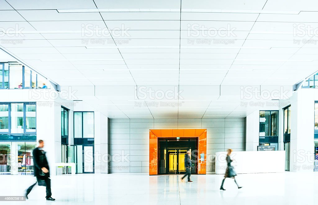Blurred Businesspeople walking inside a modern building stock photo