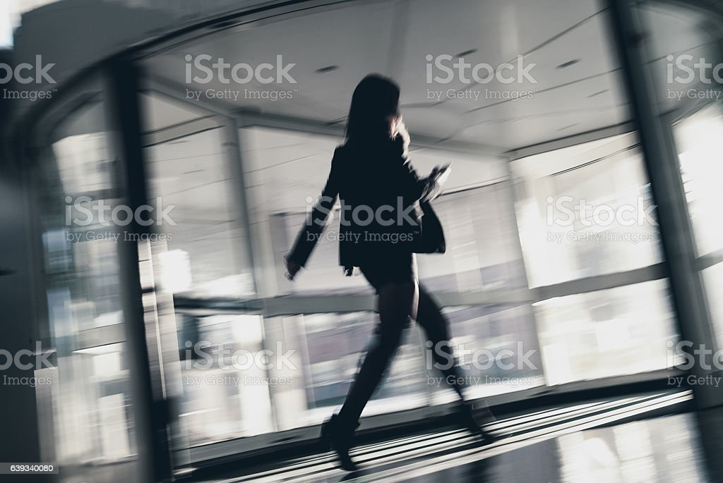 Blurred Businesswoman Walking Through Office Entrance Using Smart Phone stock photo