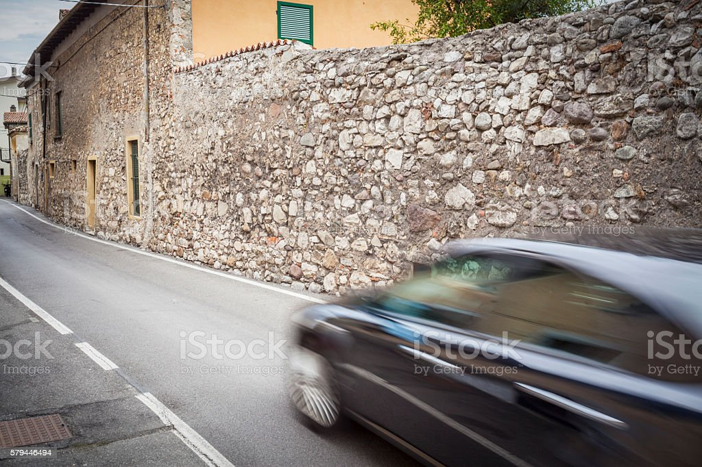 Blurred Car Passing On Street With Stone Wall stock photo