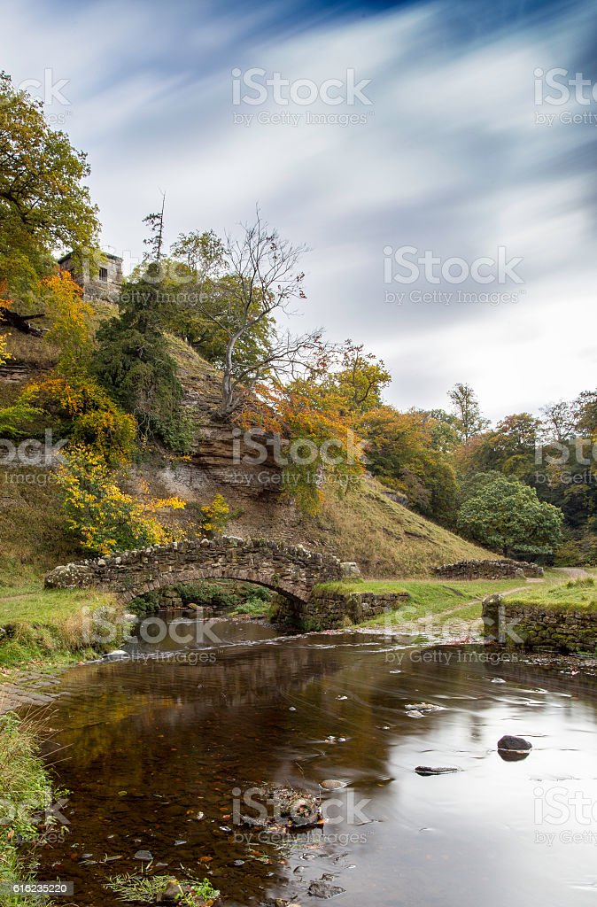 Blurred clouds over stone bridge at Fountains Abbey stock photo