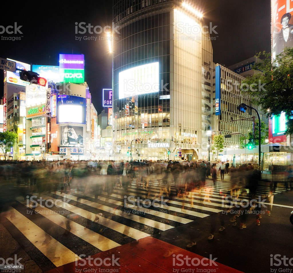 Blurred crowd crossing Shibuya in Tokyo at night stock photo