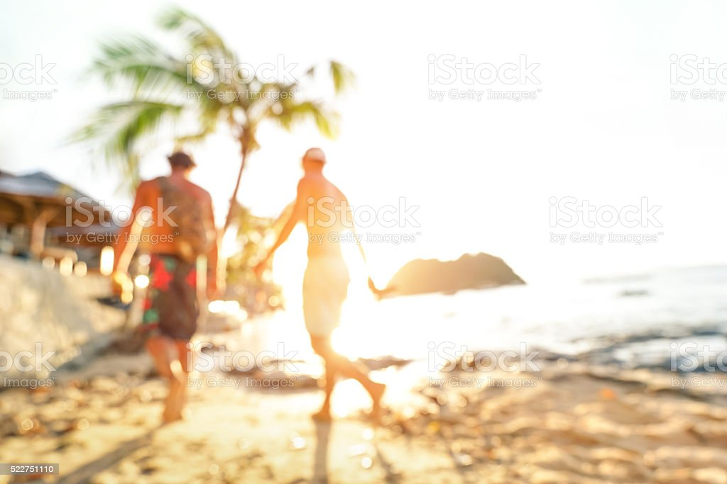 Blurred defocused silhouette of travelers at beach during sunset stock photo