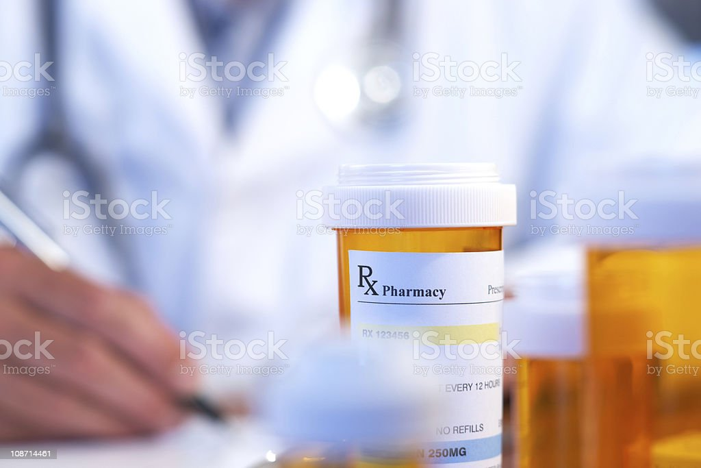 Blurred doctor behind orange prescription bottle stock photo