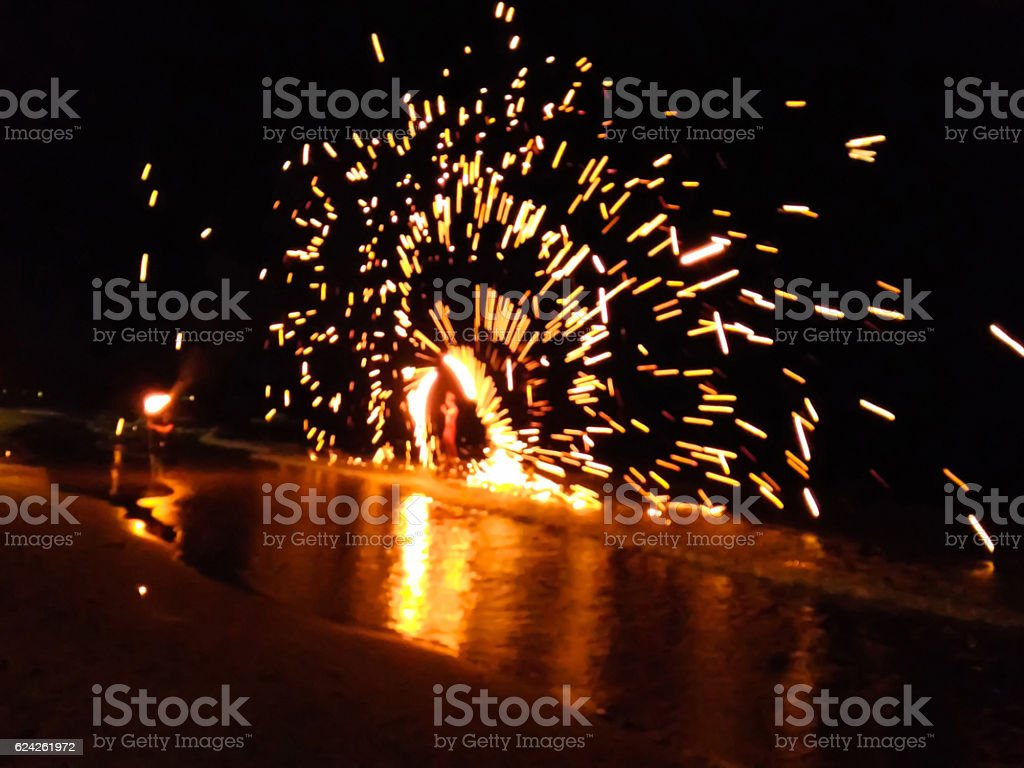 Blurred fire performer spinning fire baton  on the beach stock photo