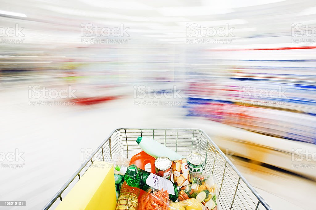Blurred, ghostlike supermarket aisles with racing, filled shopping cart royalty-free stock photo