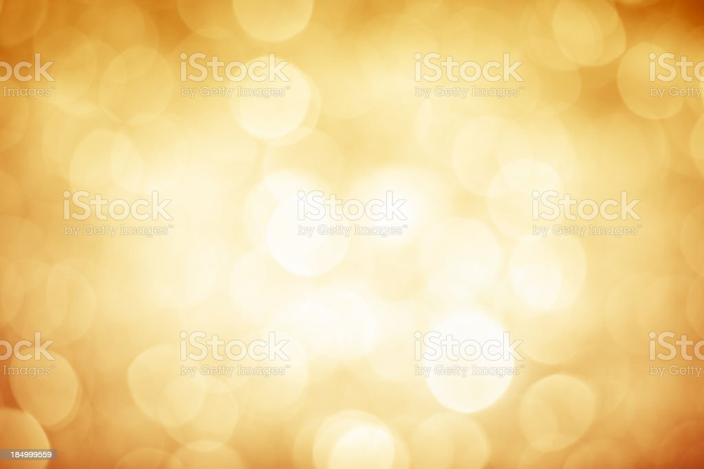 Blurred gold sparkles background with darker corners and bright center stock photo
