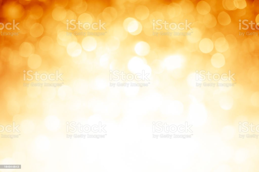 Blurred gold sparkles background with darker top corners stock photo