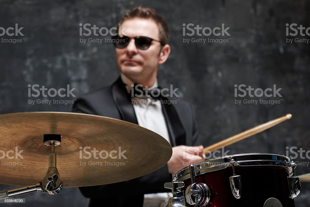 Blurred handsome man in sunglasses and suit playing a drum stock photo