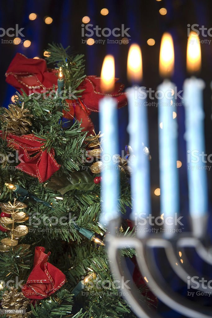 Blurred hanukkah menorah in front of Christmas pine tree stock photo
