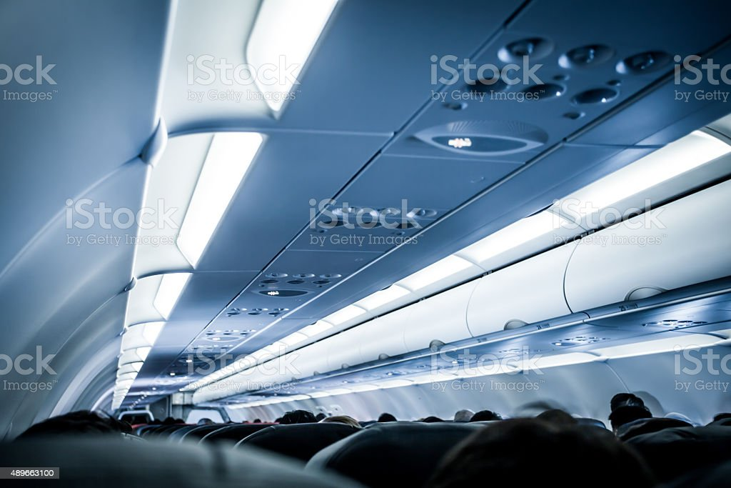 Blurred image of airplane interior in blue color filter stock photo