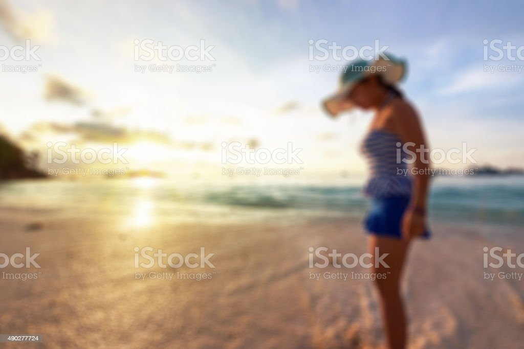 Blurred image woman on the beach at sunrise stock photo