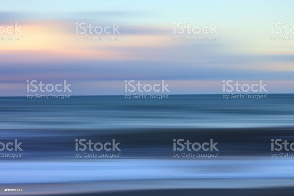 Blurred landscape: defocused sea at sunrise, moody colors stock photo