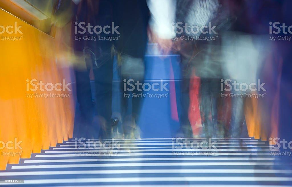 Blurred Legs of Walking People on Orange Stairs royalty-free stock photo
