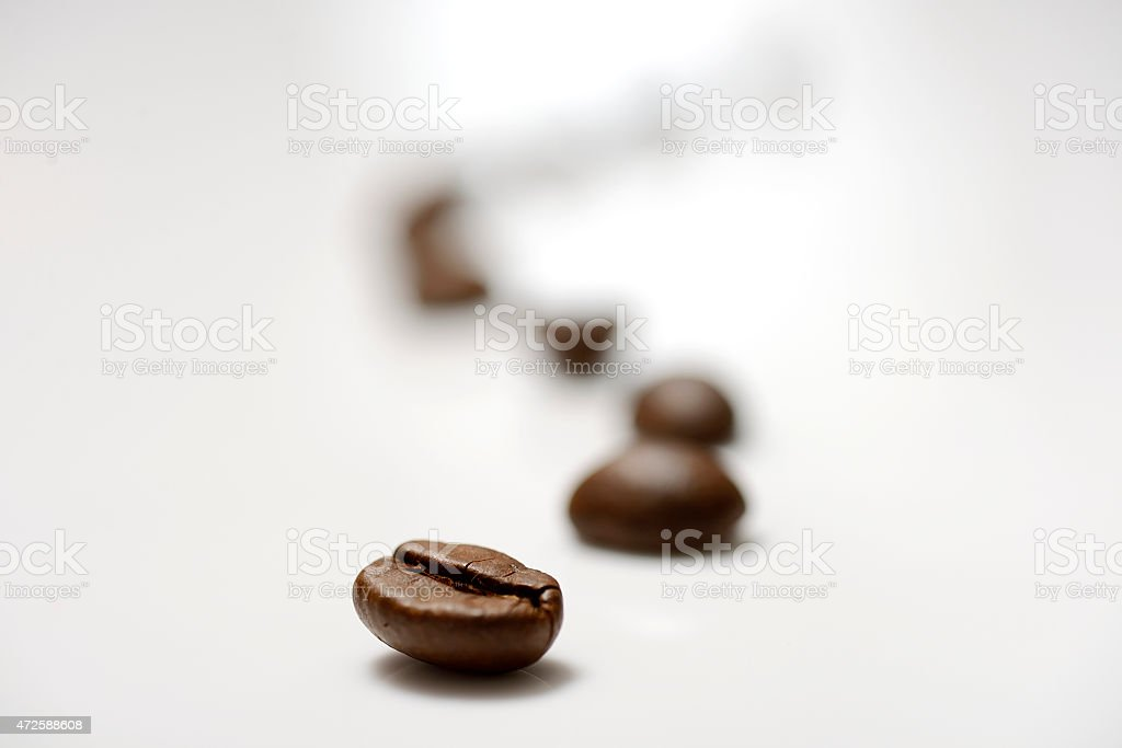A blurred line of coffee beans on white stock photo