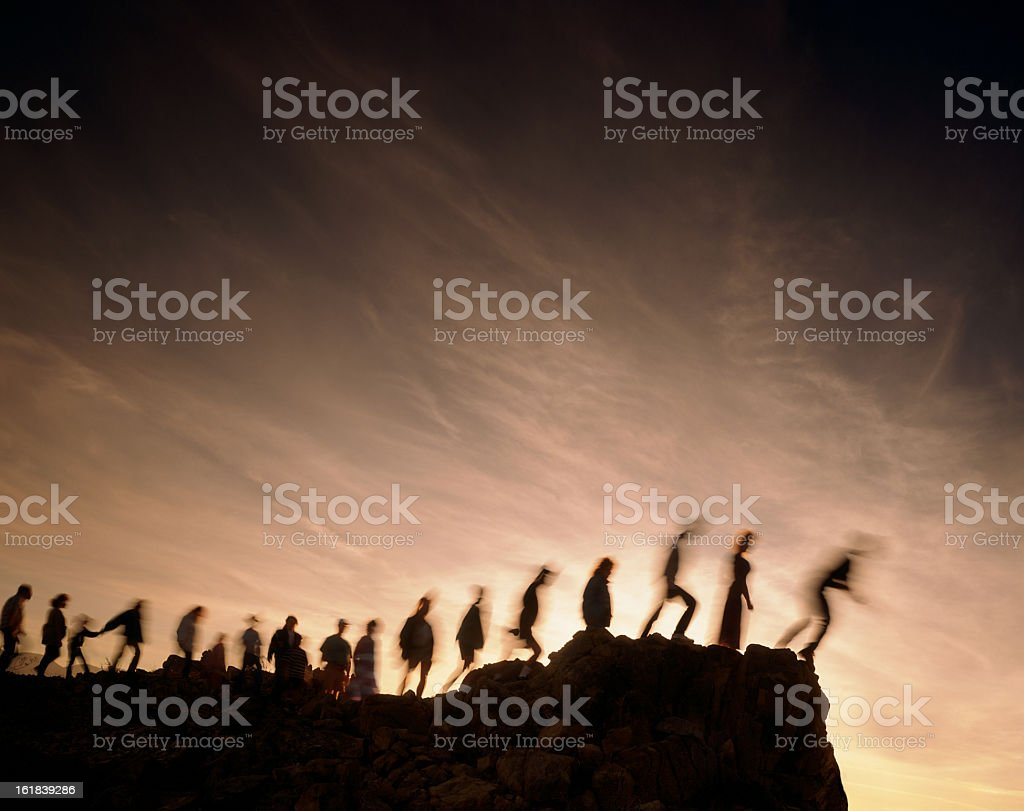 Blurred line of people on the edge of a cliff stock photo