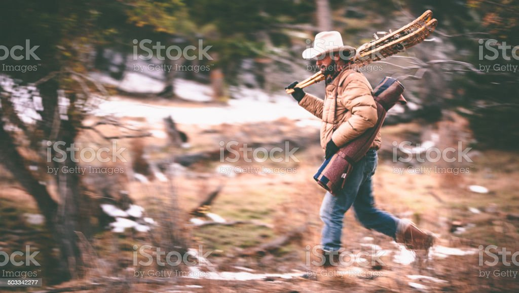 Blurred motion as man carries camping gear through woods stock photo