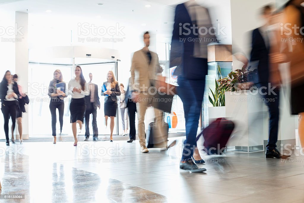 Blurred motion of business people walking at convention center stock photo