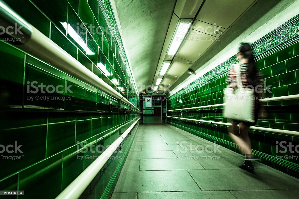 Blurred motion of young woman in London subway tunnel stock photo